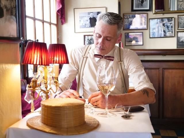 Ein Mann im Retro-Look sitzt schreibend in einem Restaurant.