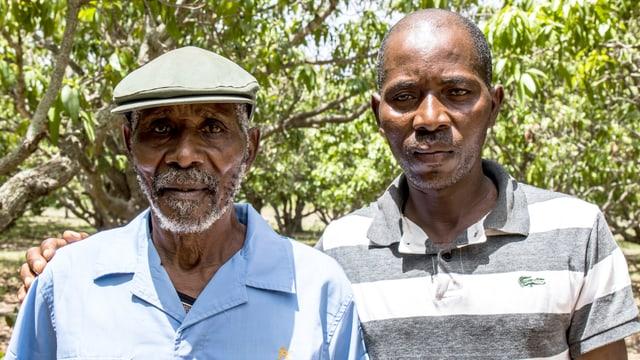Zwei Männer stehen unter einem Baum und schauen in die Kamera.