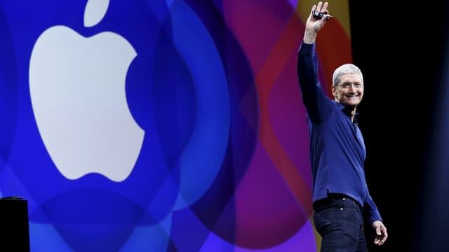 Tim Cook hält bei einer Präsentation eine Hand hoch, hinter ihm das Apple-Logo ganz gross.