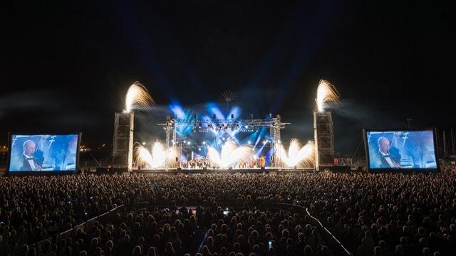Blick von weitem auf eine grosse Bühne mit einem Orchester. Auf der Bühne ist Feuerwerk zu sehen.