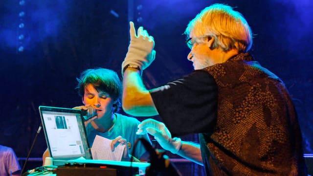 Ein Mann sitzt vor einem Laptop und hat die linke Hand angehoben, ein Junge singt in ein Mikrofon.