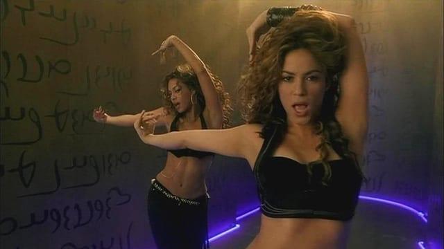 Shakira und Beyoncé tanzen. Im Hintergrund ist eine Wand mit scheinbar arabischen Schriftzeichen.