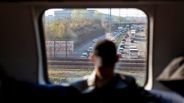 Ein Mann sieht ais einem Zug den Autostau auf der Autobahn