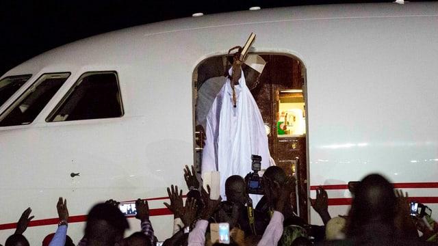 Jammeh in weissem Gewand winkt vom Eingang des Flugzeugs.