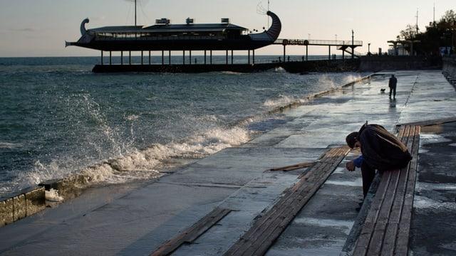 Ein Mann sitzt an einem Hafen auf der Krim und blickt nachdenklich zu Boden.
