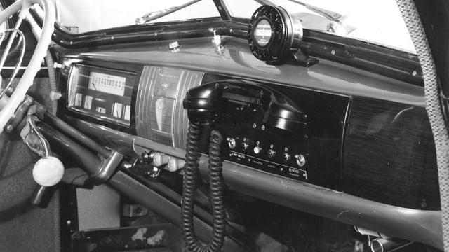 Telefonhörer und Wählscheibe an Auto-Armaturenbrett.