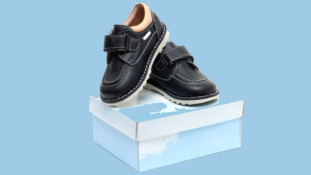 Schwarze Kinderschuhe auf einem Schuhkarton.
