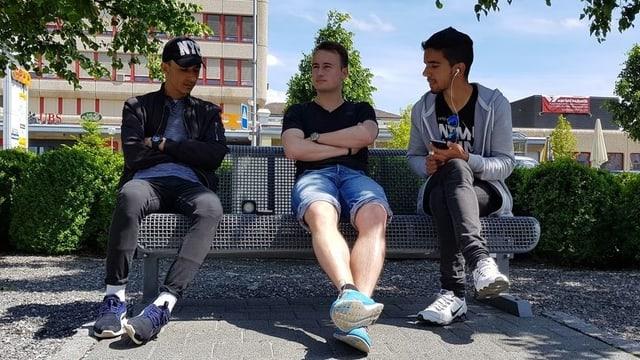 Simon Hutmacher und zwei weitere Bewohner sitzen auf einer Parkbank.