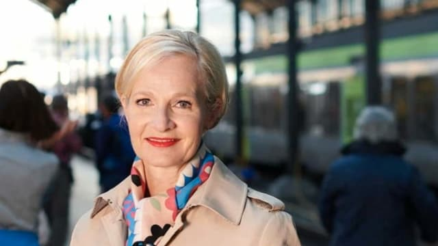 Portrait einer Frau vor Zügen im Bahnhof.