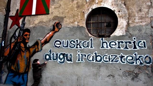 Graffiti an Wand mit baskischem Spruch