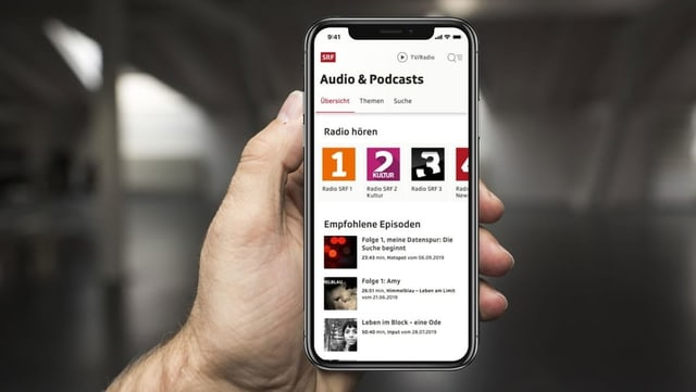 Smartphone mit neuer Podcastseite von SRF in einer Hand.