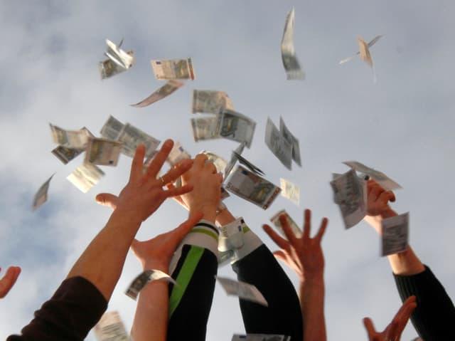 Hände strecken sich nach vom Himmel fallenden Euro-Scheine aus.