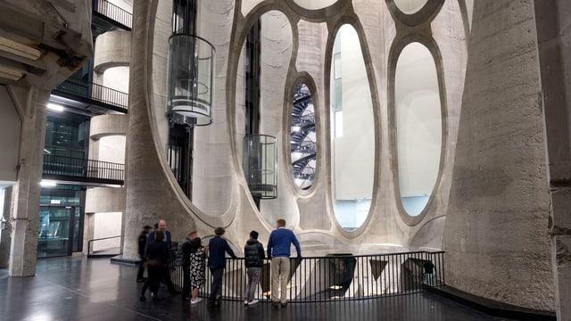 Ein Innenraum aus Beton. Die Wände sind mit runden Löchern geöffnete Röhren in denen gläserne Lifte fahren.