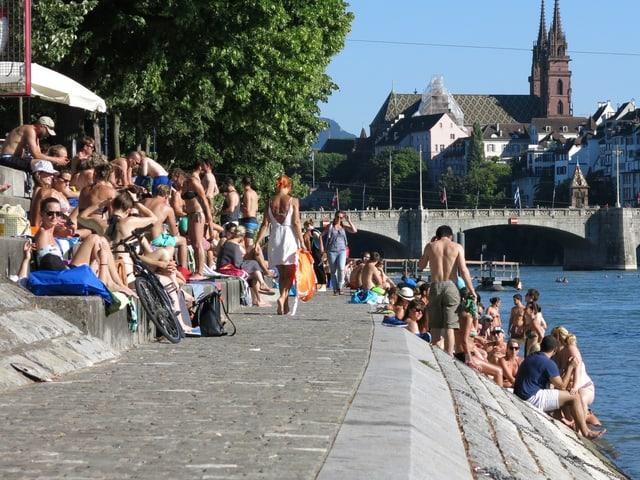 Leute beim Sonnenbaden am Rheinufer.