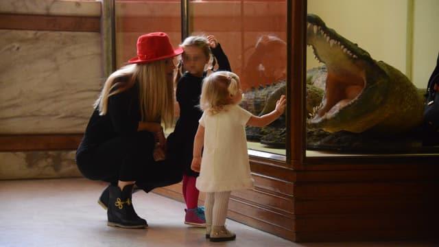 Eine Frau kniet mit ihren beiden Kindern vor einer Glasbox, in der ein ausgestopftes Krokodil ist.