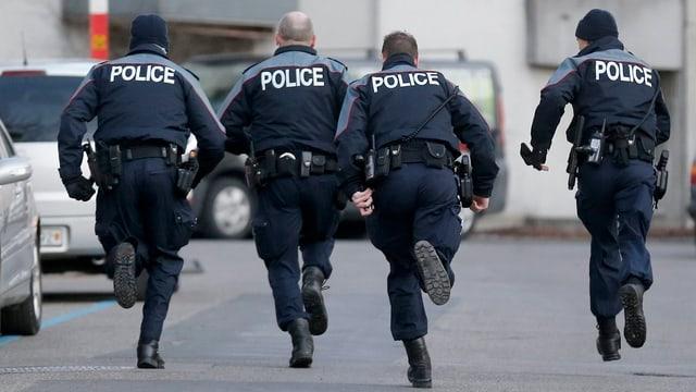 Vier Polizisten (von hinten) rennen eine Strasse entlang.