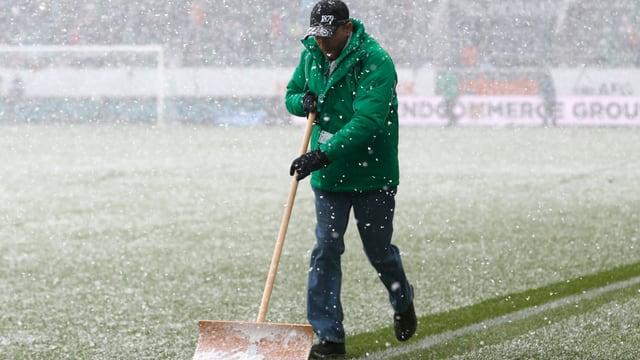 Ein Helfer räumt den Schnee vom Spielfeld in St. Gallen.