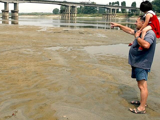 Grossvater mit Kind auf den Schultern wandert durch das trocken Flussbett, Juni 2003 Fluss Po.