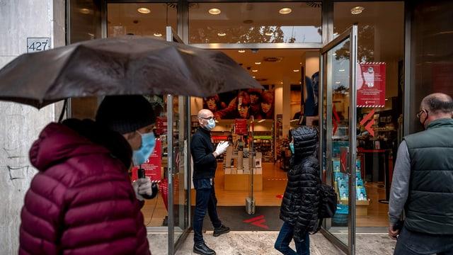 Menschen mit Masken vor einem italienischen Buchladen.