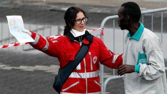 Eine Angehörige des Roten Kreuzes zeigt einem im Hafen von Catania angekommenen schwarzen Flüchtling mit der Hand den Weg