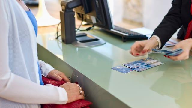 Frau steht am Bankschalter, Angestellte zählt 100er-Noten auf den Tresen.