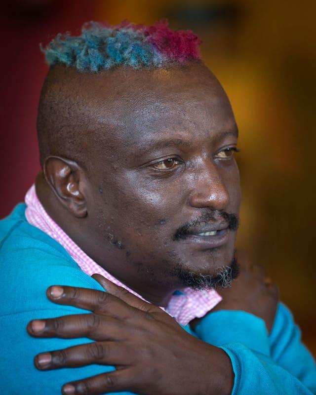 Porträt von der Seite. Binyavanga Wainaina hält die Arme über der Brust gekreuzt und spricht.