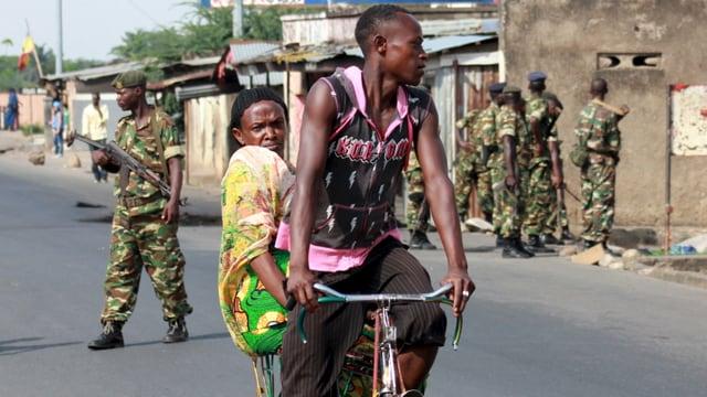 Soldaten patroullieren in einem Vorort von Bujumbara, davor fahren ein Mann und eine Frau auf einem Fahrrad.