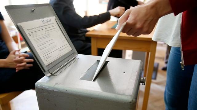Hand wirft Abstimmungszettel in eine Urne
