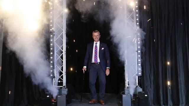 Der Wahlgewinner Norbert Hofer schreitet durch einen mit Feuerwerkskörpern geschmückten Rahmen.