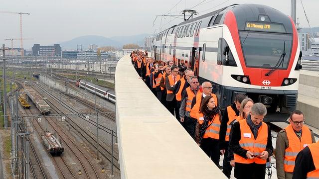 S-Bahn auf einer Brücke stehend, Personen mit Schutzwesten