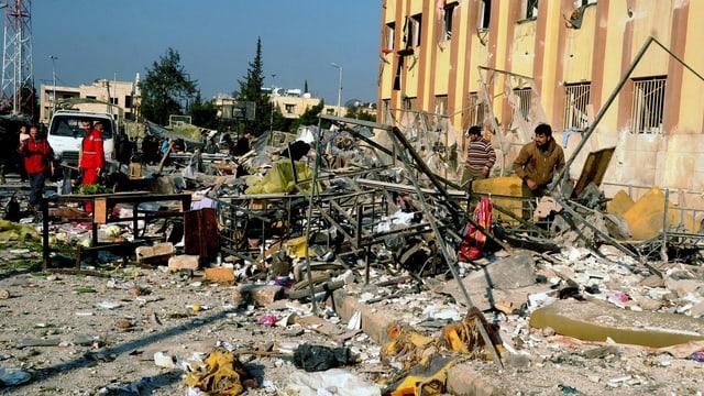 Sanitäter und Helfer in Aleppo suchen vor dem völlig zerstörten Uni-Gebäude nach Verletzten. (keystone)