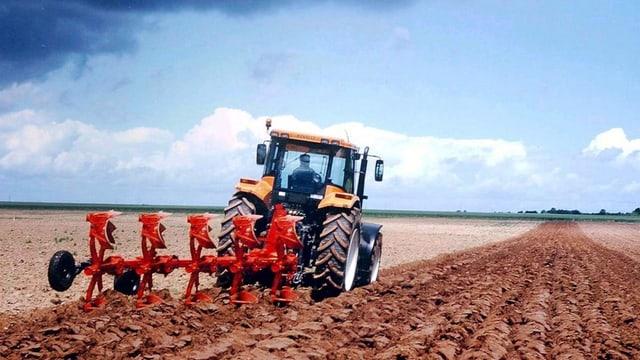 Ein Traktor mit rotem Pflug zieht Furchen in eine rotbräunliches Feld. Darüber ein hellblauer Himmel mit weissen Wolken.