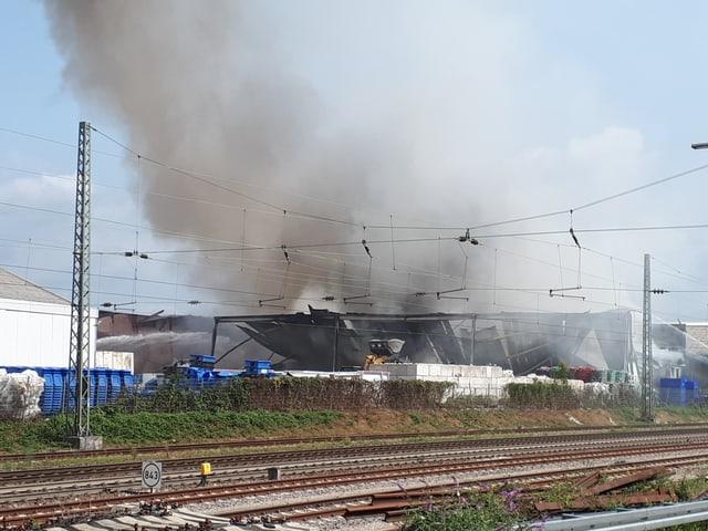 Die betroffene Halle steht in Vollbrand und ist mittlerweile eingestürzt.
