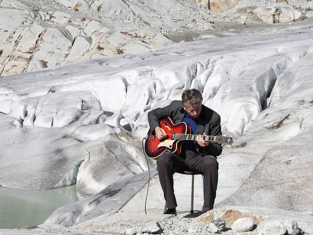 Ein Mann spielt auf einem Gletscher Gitarre.