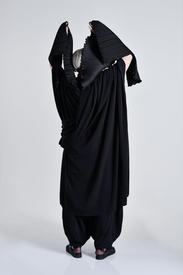 Eine Frau trägt Schwarz und wird von hinten fotografiert.