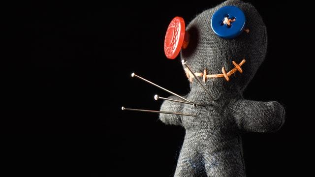 Vier Nadeln stecken in einer grauen Voodoo-Puppe mit Knöpfen als Auge.