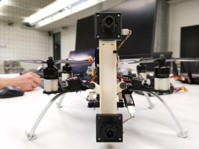 Eine Drohne steht auf vier Füssschen auf einem Tisch, zwei Kameralinsen sind vorne montiert.