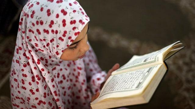 Ein Mädchen mit Kopftuch liest den Koran.
