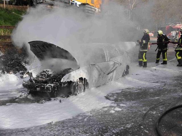 Ausgebranntes Auto und Feuerwehrleute.