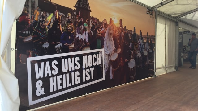 Ein grossformatiges Plakat mit einem Foto der Basler Fasnacht und dem Spruch: Was uns hoch & heilig ist.