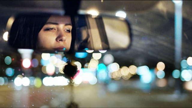 Die 18-jährige Prostituierte Mia spiegelt sich im Rückspiegel eines Autos.