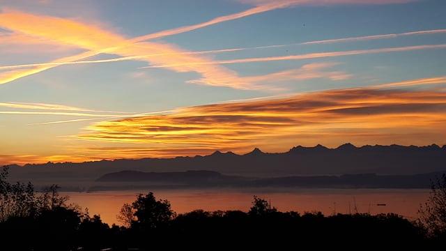 Blick über den Neuenburgersee zu den Alpen, darüber ein paar Schleierwolken.