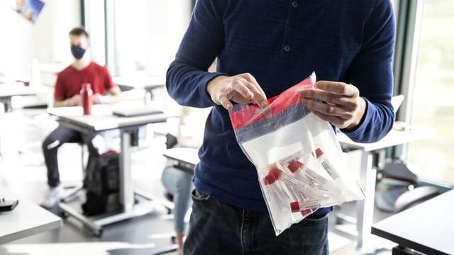 Ein Lehrer sammelt die Becherchen in einer Plastiktasche.