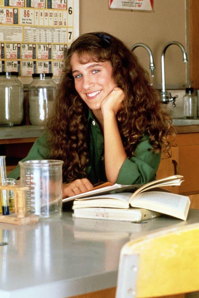 Junge Frau stützt Kopf auf die Hand und lächelt in Kamera. Vor ihr liegen Bücher auf dem Tisch.