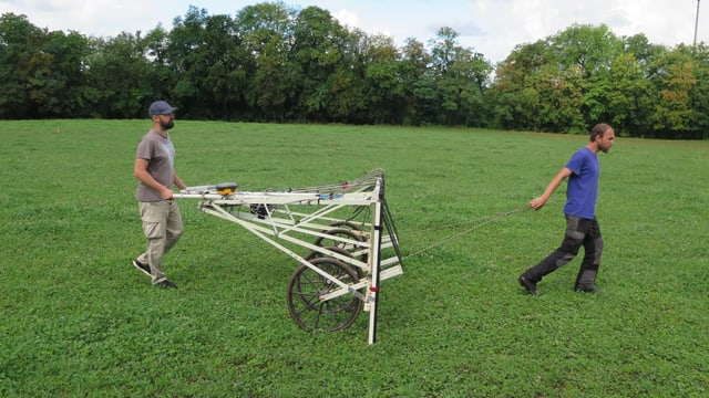 Zwei Männer ziehen ein grosses Gerät über ein Feld