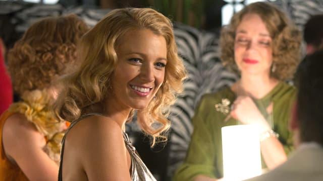 Eine Blondine mit langen Locken in festlicher Stimmung, hinter ihr weitere festlich zurechtgemachte Frauen.