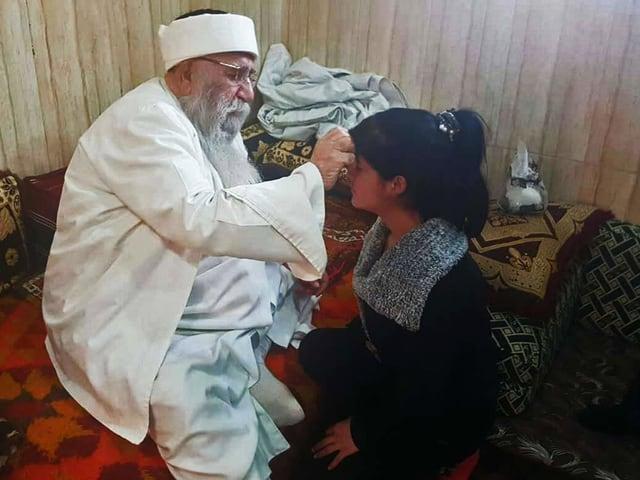 Baba Sheikh macht einer jungen Frau ein Kreuzzeichen auf die Stirne.