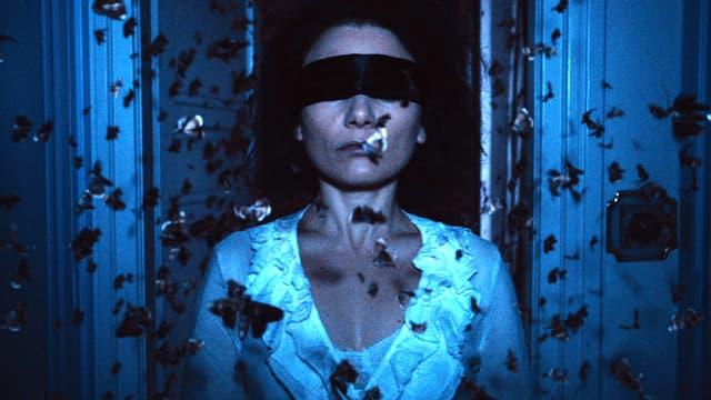Eine Frau mit Augenbinde steht in einem Schwarm von Nachtfaltern.