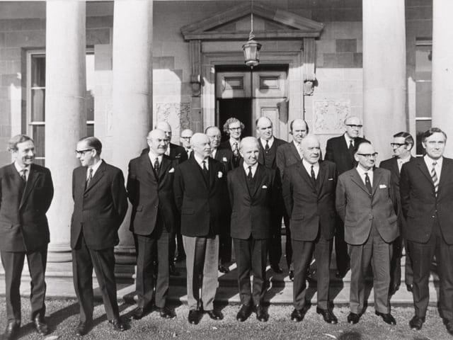 Männer der Regierung vor einem Gebäude.