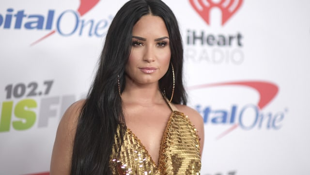 Demi Lovato vor einer weissen Fotowand.